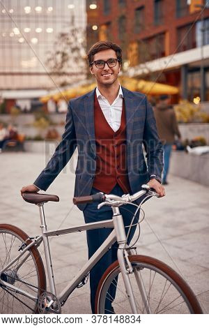 Positive Young Male In Smart Casual Clothes And Glasses Smiling And Looking At Camera While Standing