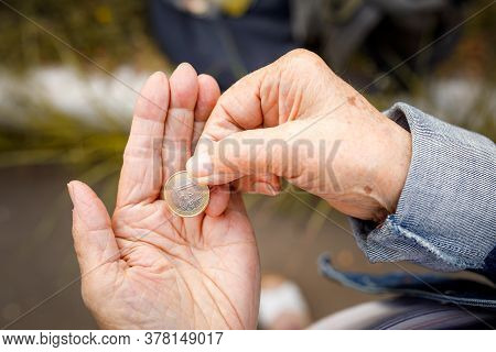 One Euro Coin In The Hands Of An Elderly Lady. Poverty Concept, No Retirement Savings