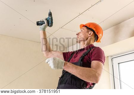 Installation Of Drywall. Worker Is Using Screws And A Screwdriver To Attach Plasterboard To The Ceil