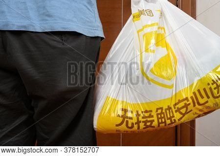 Zhongshan,china-july 6,2020:man Delivering A Meituan Pack To The Customers Home.meituan Not Only Del