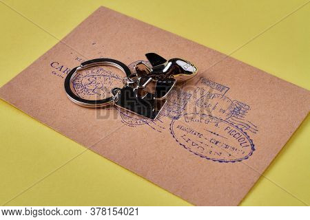 International Vintage Post Mail Concept. Metal Trinket On A Letter Isolated On Yellow Background.