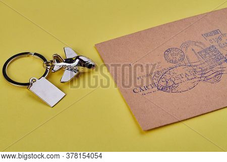 Metal Key Plane Trinket And Beige Envelope. Isolated On Yellow Background.