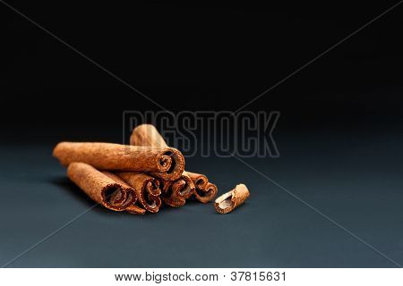 Cinnamon Sticks On Grey And Black Background
