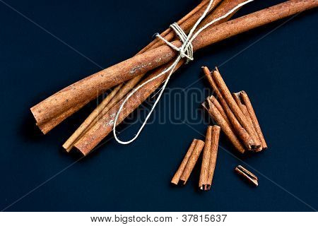 Cinnamon Bunch And Loose Sticks On Deep Blue Background