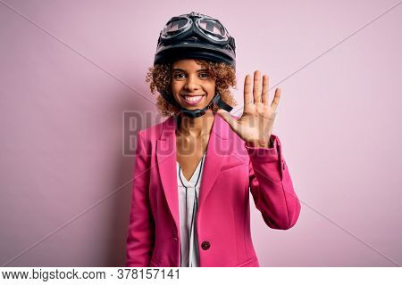African american motorcyclist woman with curly hair wearing moto helmet over pink background showing and pointing up with fingers number five while smiling confident and happy.