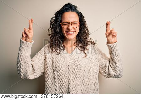 Beautiful woman with curly hair wearing casual sweater and glasses over white background gesturing finger crossed smiling with hope and eyes closed. Luck and superstitious concept.