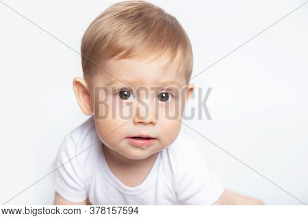Caucasian Baby Boy Drooling Dressed In A White T-shirt On A White Background Closeup