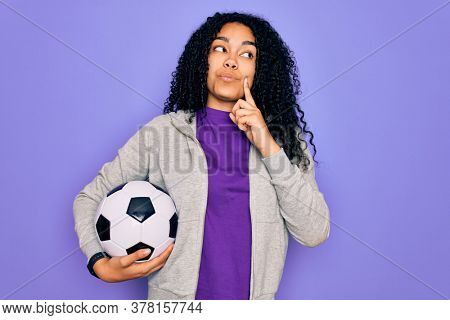 African american curly player woman playing soccer holding football bal over purple background serious face thinking about question, very confused idea