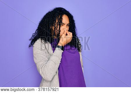 Young african american sporty woman wearing casual sweatshirt over purple background smelling something stinky and disgusting, intolerable smell, holding breath with fingers on nose. Bad smell