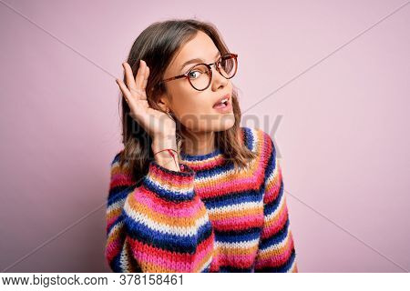 Young beautiful blonde girl wearing glasses and casual sweater over pink isolated background smiling with hand over ear listening an hearing to rumor or gossip. Deafness concept.
