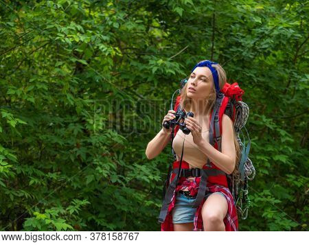 Portrait Of A Hiker Woman With A Backpack Walks Through The Forest With Binoculars.