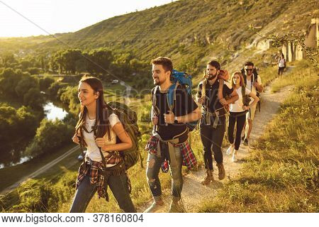 Young People With Backpacks Walking Along Narrow Path In Mountains. Group Of Cheerful Tourists Hikin