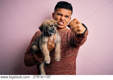 Young handsome latin man holding cute puppy pet over isolated pink background annoyed and frustrated shouting with anger, crazy and yelling with raised hand, anger concept