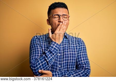 Young handsome latin man wearing casual shirt and glasses over yellow background bored yawning tired covering mouth with hand. Restless and sleepiness.