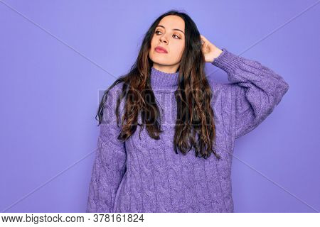 Young beautiful woman wearing casual turtleneck sweater standing over purple background confuse and wondering about question. Uncertain with doubt, thinking with hand on head. Pensive concept.