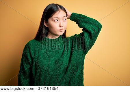 Young beautiful asian woman wearing green winter sweater over yellow isolated background confuse and wondering about question. Uncertain with doubt, thinking with hand on head. Pensive concept.