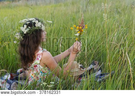 Girl In The Field. Side View Of A Sitting Girl With Long Hair In A Wreath Of Wildflowers. The Girl E