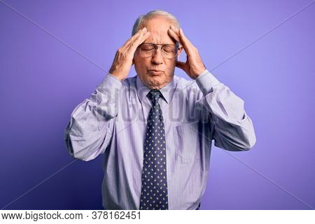 Grey haired senior business man wearing glasses standing over purple isolated background with hand on head for pain in head because stress. Suffering migraine.