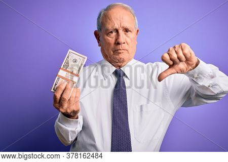 Senior grey haired man holding bunch of fifty dollars banknotes over purple background with angry face, negative sign showing dislike with thumbs down, rejection concept