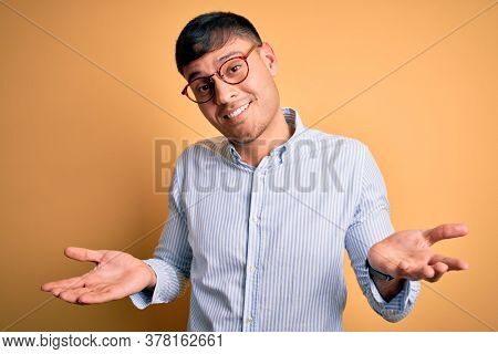 Young handsome hispanic business man wearing nerd glasses over yellow background clueless and confused expression with arms and hands raised. Doubt concept.