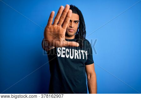 Young african american afro safeguard man with dreadlocks wearing security uniform with open hand doing stop sign with serious and confident expression, defense gesture