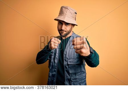 Handsome tourist man with beard on vacation wearing explorer hat over yellow background Punching fist to fight, aggressive and angry attack, threat and violence