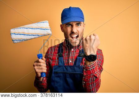 Young handsome painter man painting wall using roller over isolated yellow background annoyed and frustrated shouting with anger, crazy and yelling with raised hand, anger concept