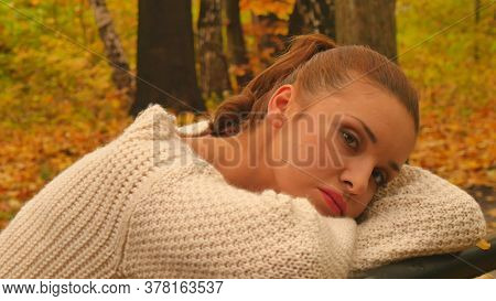Autumn depression. Young sad and lonly woman outdoor.