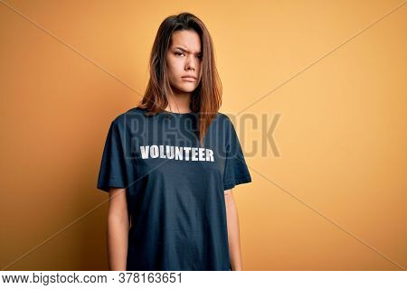 Young beautiful brunette girl doing volunteering wearing t-shirt with volunteer message word skeptic and nervous, frowning upset because of problem. Negative person.