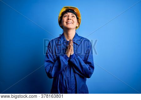 Young beautiful worker woman with blue eyes wearing security helmet and uniform begging and praying with hands together with hope expression on face very emotional and worried. Begging.