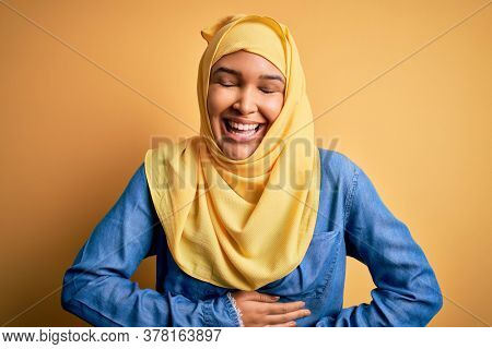 Young beautiful woman with curly hair wearing arab traditional hijab over yellow background smiling and laughing hard out loud because funny crazy joke with hands on body.