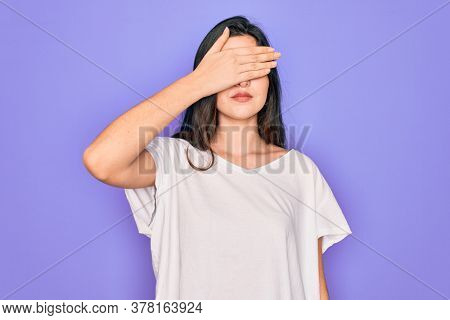Young beautiful brunette woman wearing casual white t-shirt over purple background covering eyes with hand, looking serious and sad. Sightless, hiding and rejection concept