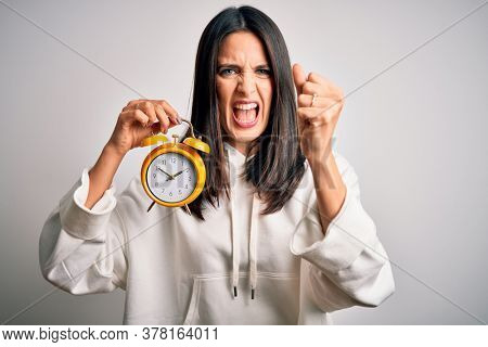 Young woman with blue eyes holding alarm clock standing over isolated white background annoyed and frustrated shouting with anger, crazy and yelling with raised hand, anger concept