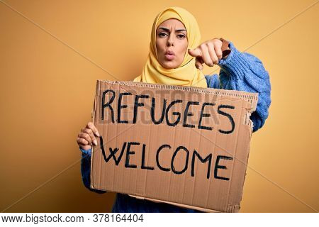 Beautiful arab woman wearing islamic hijab holding banner with refugees welcome message pointing with finger to the camera and to you, hand sign, positive and confident gesture from the front