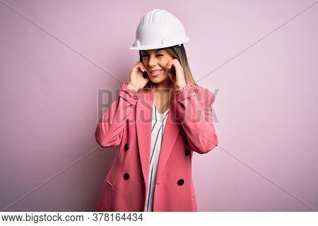 Young beautiful brunette architect woman wearing safety helmet over pink background covering ears with fingers with annoyed expression for the noise of loud music. Deaf concept.