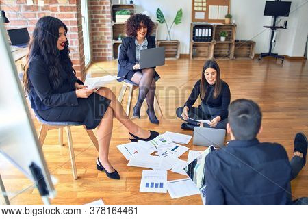 Group of business workers smiling happy and confident. Sitting on the floor relaxed with smile on face. Working together reading documents and speaking at the office