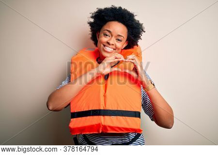 Young African American afro woman with curly hair wearing orange protection lifejacket smiling in love doing heart symbol shape with hands. Romantic concept.