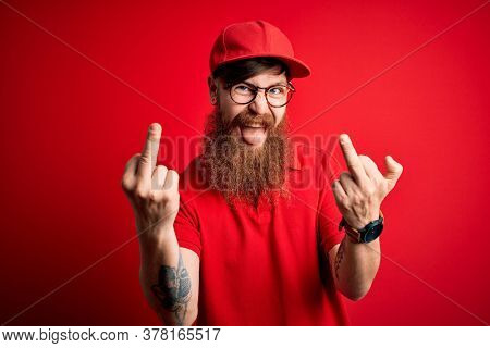 Young handsome delivery man wearing glasses and red cap over isolated background Showing middle finger doing fuck you bad expression, provocation and rude attitude. Screaming excited