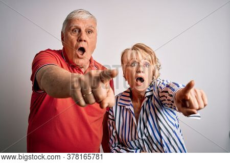 Senior beautiful couple standing together over isolated white background Pointing with finger surprised ahead, open mouth amazed expression, something on the front