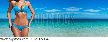 Woman with perfect body in blue bikini over tropical sea background
