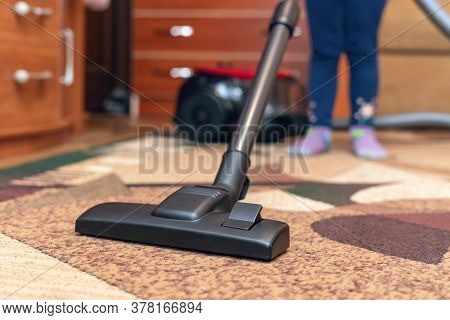 A Small Child Vacuums A Carpet With A Vacuum Cleaner.