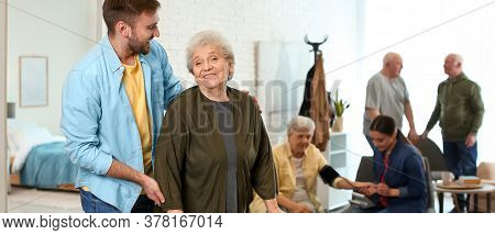 Young Man Taking Care Of Elderly Woman In Geriatric Hospice. Banner Design