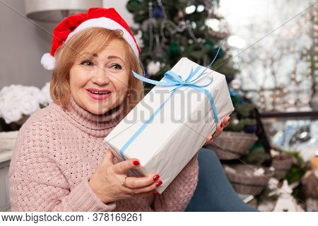 Close Up Of A Happy Senior Woman Celebrating Christmas At Home, Hugging Funny Santa Claus Toy Near X