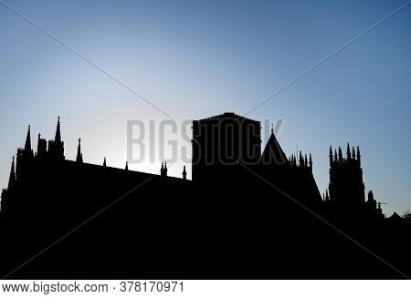 York Minster In Silhouette Back Lit Against A Morning Sunrise And Blue Sky