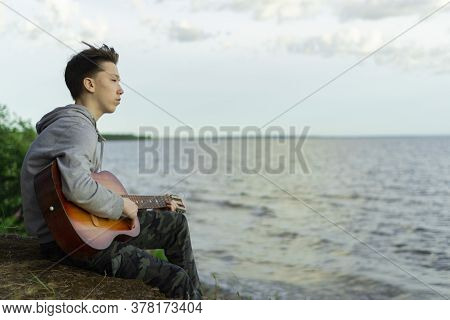 A Teenager Plays A Guitar While Sitting On The Shore Of A Lake.