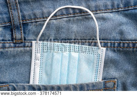 Jeans Pocket With Blue Medical Disposable Mask Close Up