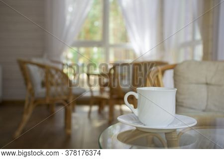 White Cup And Rattan Furniture On The Summer Porch.