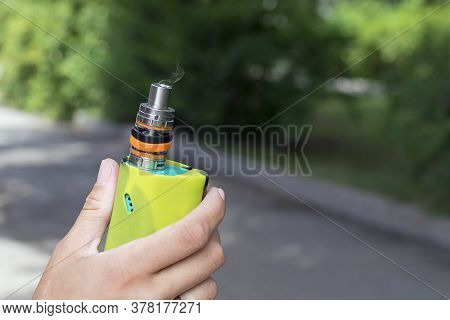 Electronic Cigarette In A Woman's Hand On The Background Of A Park. An Electronic Device That Create