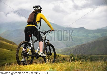 A Young Slender Girl With A Backpack And A Bicycle Helmet Sits On A Bicycle High In The Mountains On
