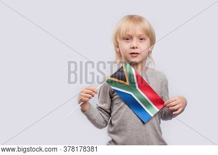 Cute Fair-haired Boy Holding Flag Of South Africa. Education In South Africa.